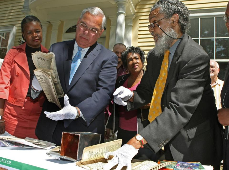 Outside the Roxbury Historical Society building this morning Mayor Thomas M. Menino,left, assisted in unveiling the contents of a 1922 time capsule that was found in the historic Ferdinand Building site in Dudley Square. in 2008.